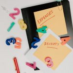 Notes for expenses and receipts with number magnets on a table